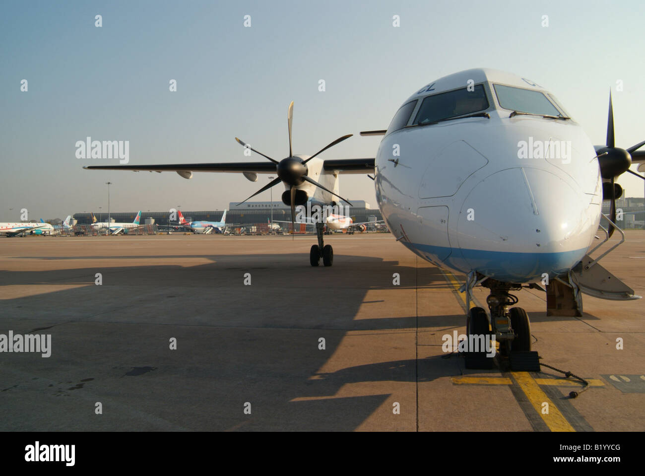 A parked Dash8 400 aircraft viewed from infront and shown against airport terminal buildings in the distance. - Stock Image