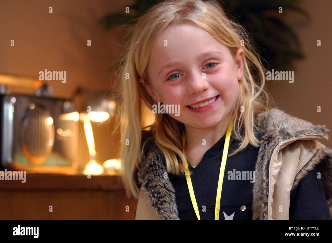 Royalty free photograph of young confident and bubbly young girl smiling at  the camera at her