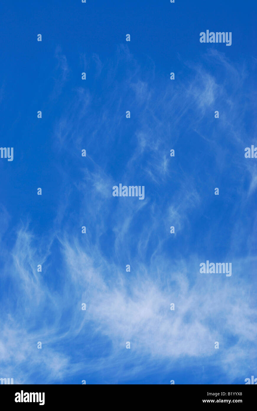 White wispy clouds against a deep blue sky - Stock Image