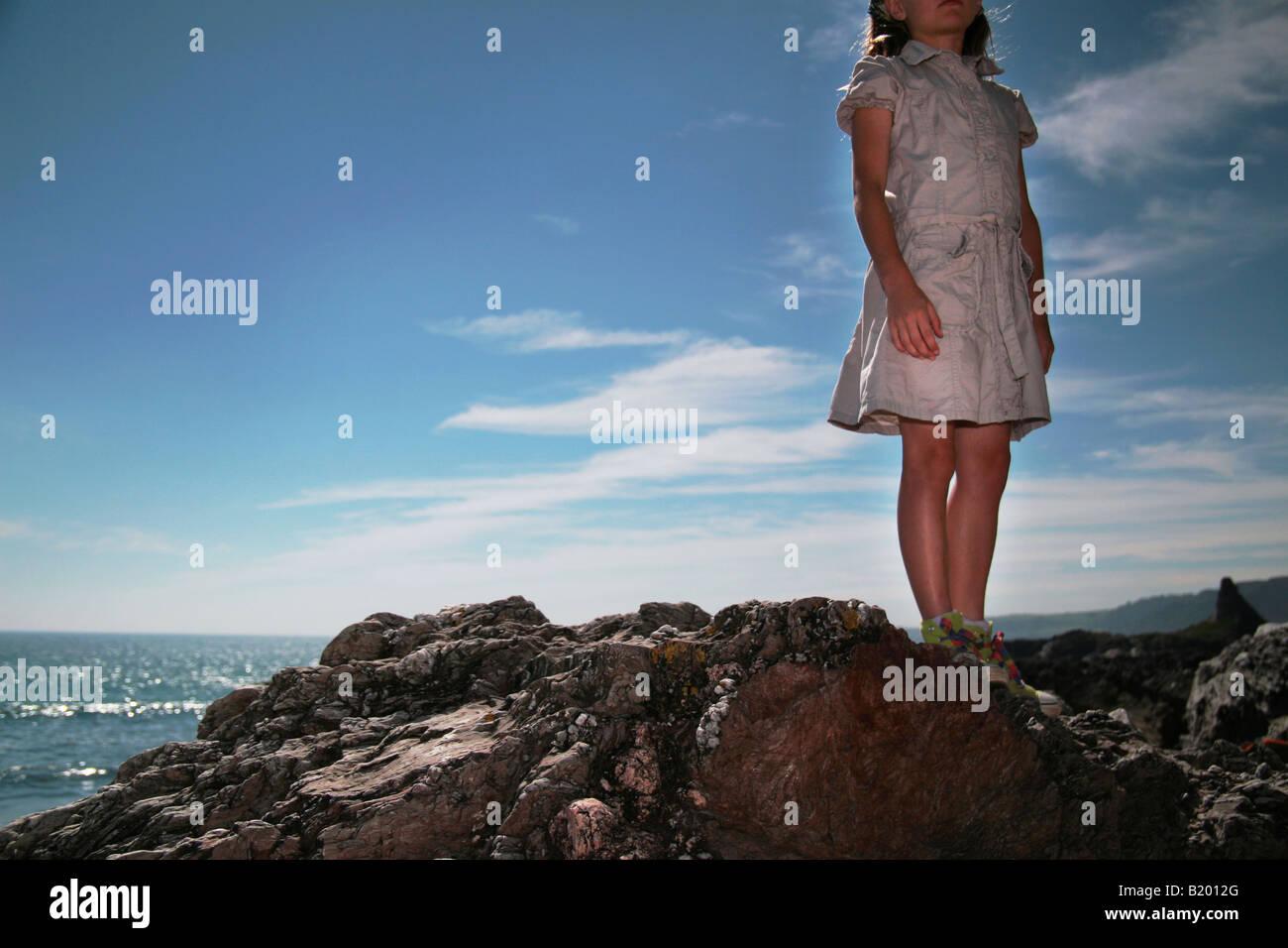 young girl stood on rocks - Stock Image