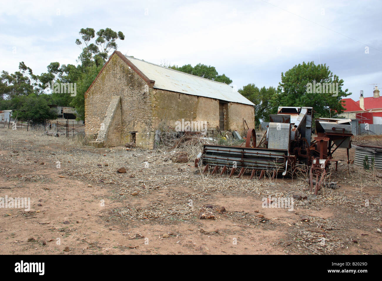 An old piece of farm machinery outside a 120 year old barn on a farm in Australia - Stock Image