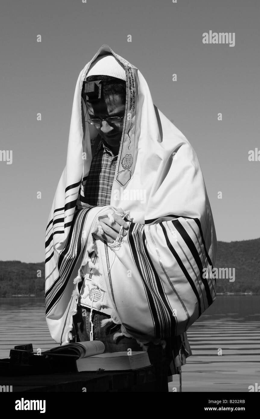 A religious Jewish man wearing tefillin and a talit doing morning prayers in the splendor of nature. - Stock Image