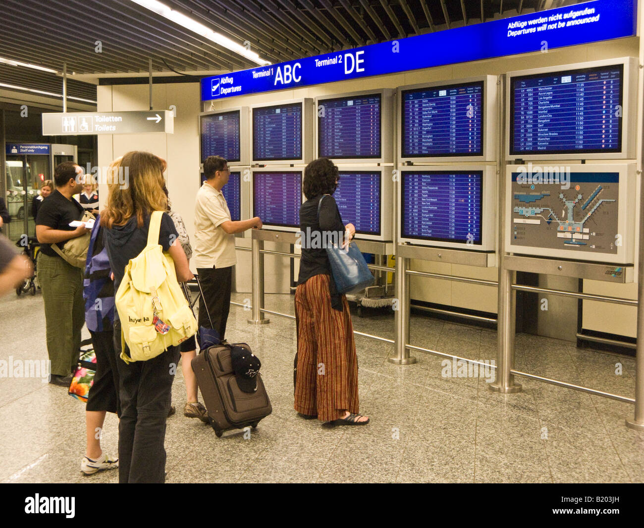 passengers looking at flight schedule video terminals, Frankfurt airport, Germany - Stock Image
