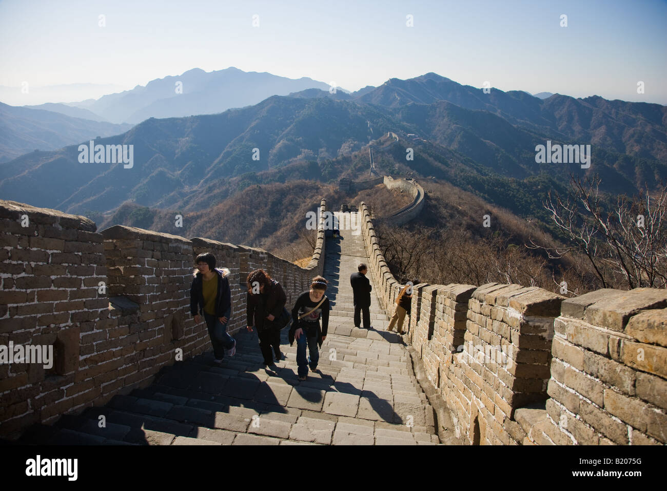 Tourists walk the ancient Great Wall of China at Mutianyu north of Beijing formerly Peking China - Stock Image