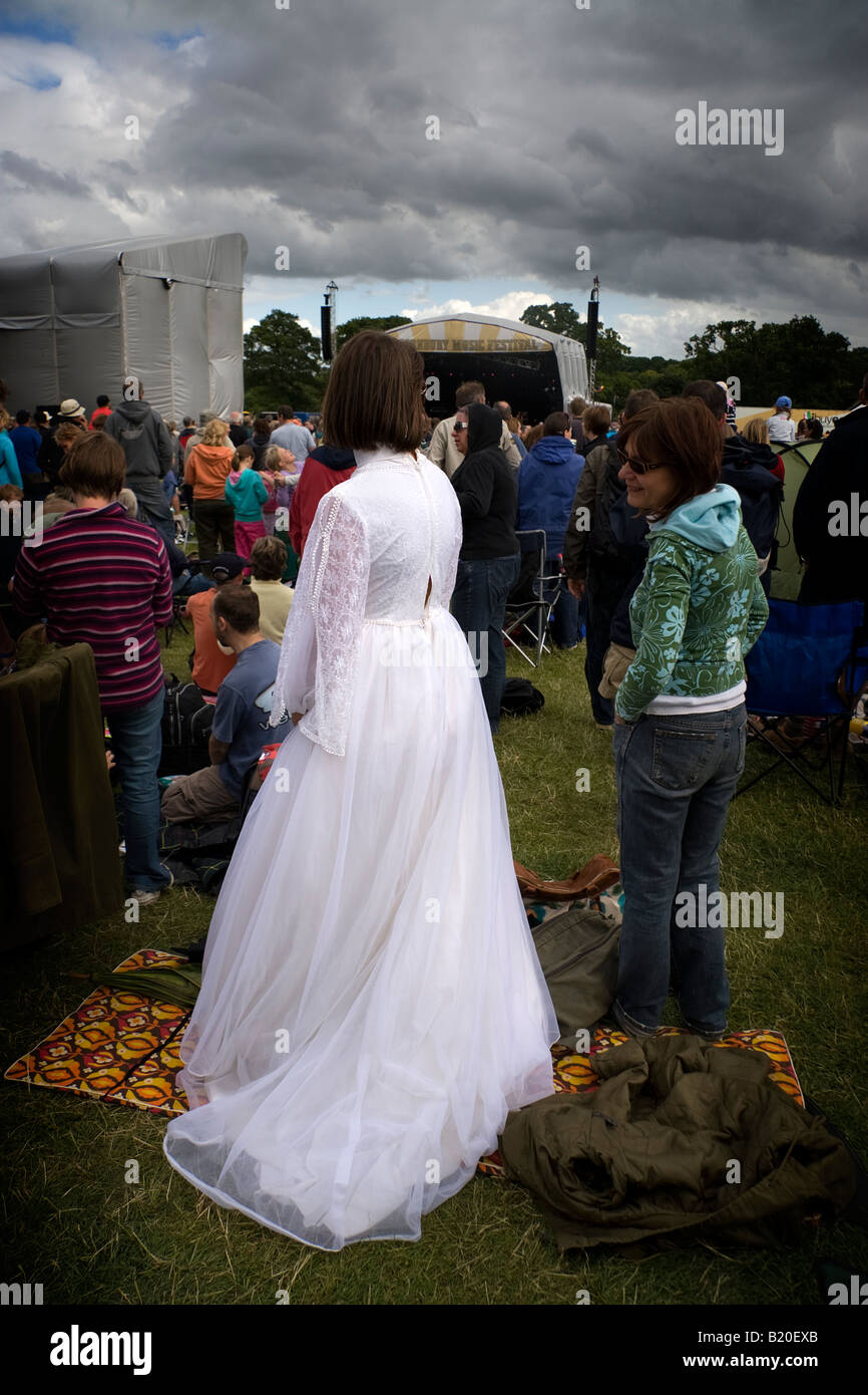 A young woman wearing a wedding dress outdoors on a cloudy day at ...