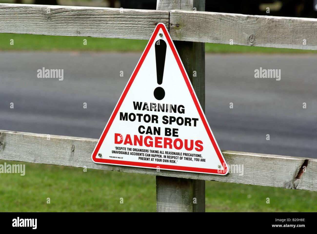 Motor Sport danger sign on track side fence - Stock Image