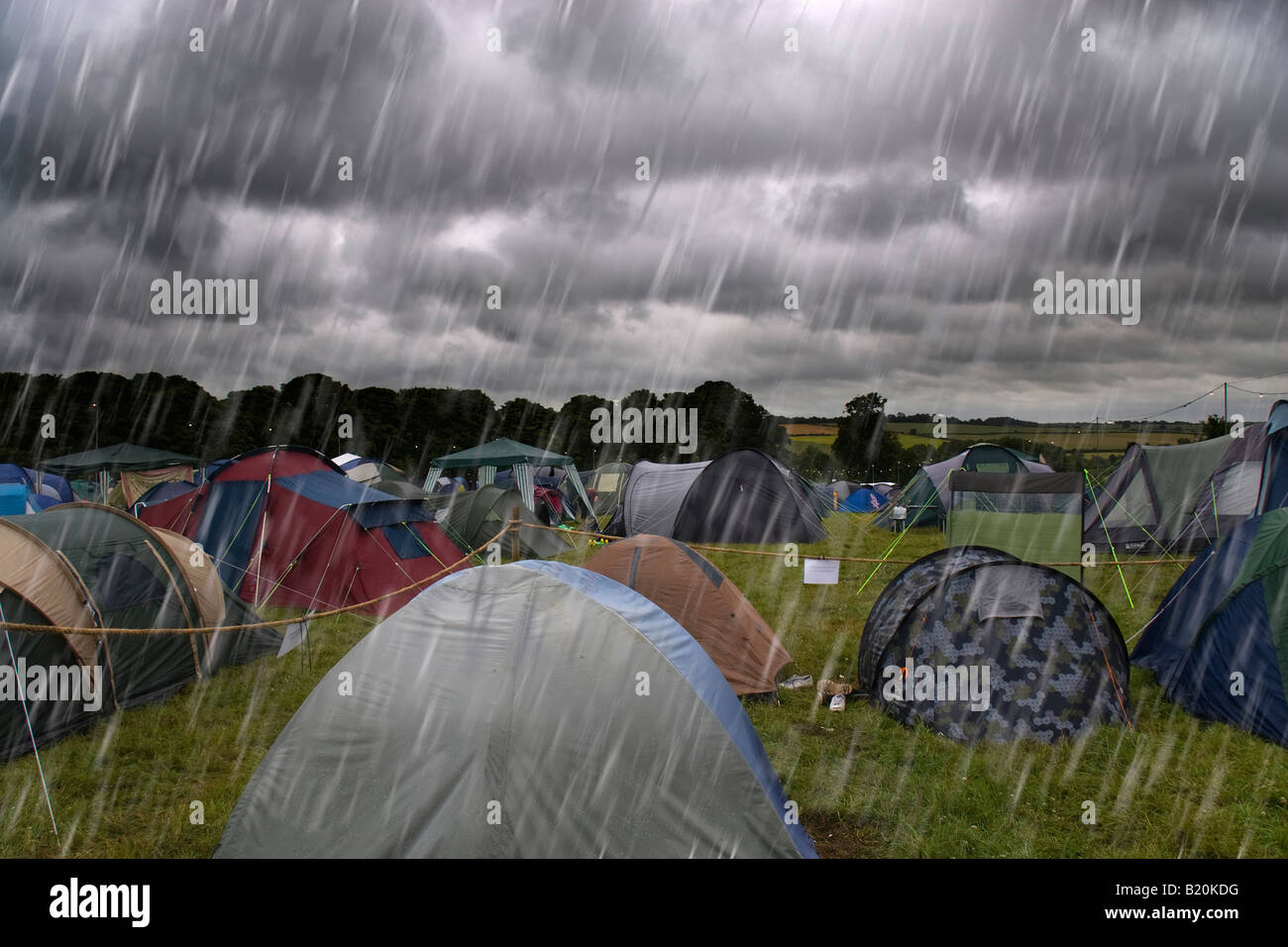 Dark clouds in the sky with torrential rain falling on tents at a campsite at the Cornbury Music Festival - Stock Image