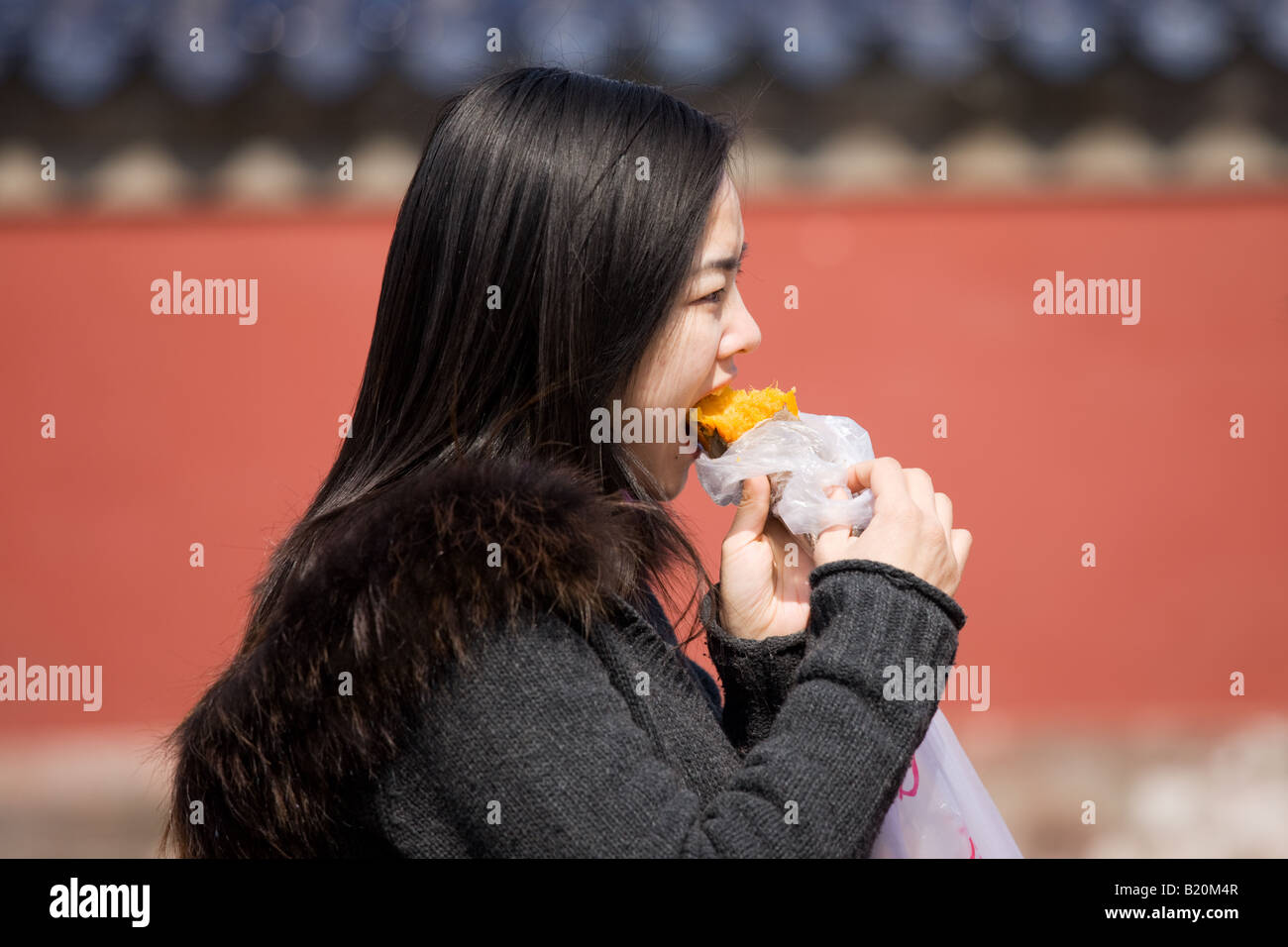 Girl eating yam sweet potato at the Ming Dynasty Temple of Heaven Beijing China - Stock Image
