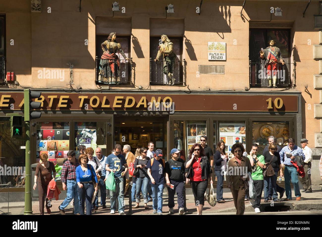 SPAIN Madrid Crowd of people in crosswalk of Paseo del Prado Statues in balconies of art store - Stock Image