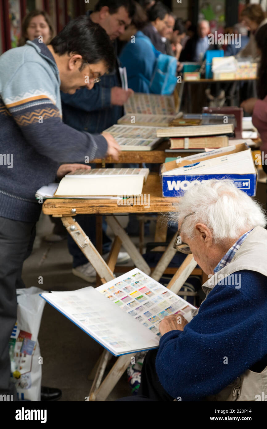 SPAIN Madrid Stamp collectors trade and sell collections in Plaza Mayor on Sunday morning Look through notebooks - Stock Image