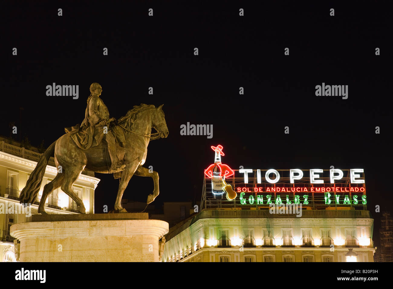 SPAIN Madrid Statue of Mounted King Charles III in Puerto del Sol plaza with Tio Pepe neon sign at night Stock Photo