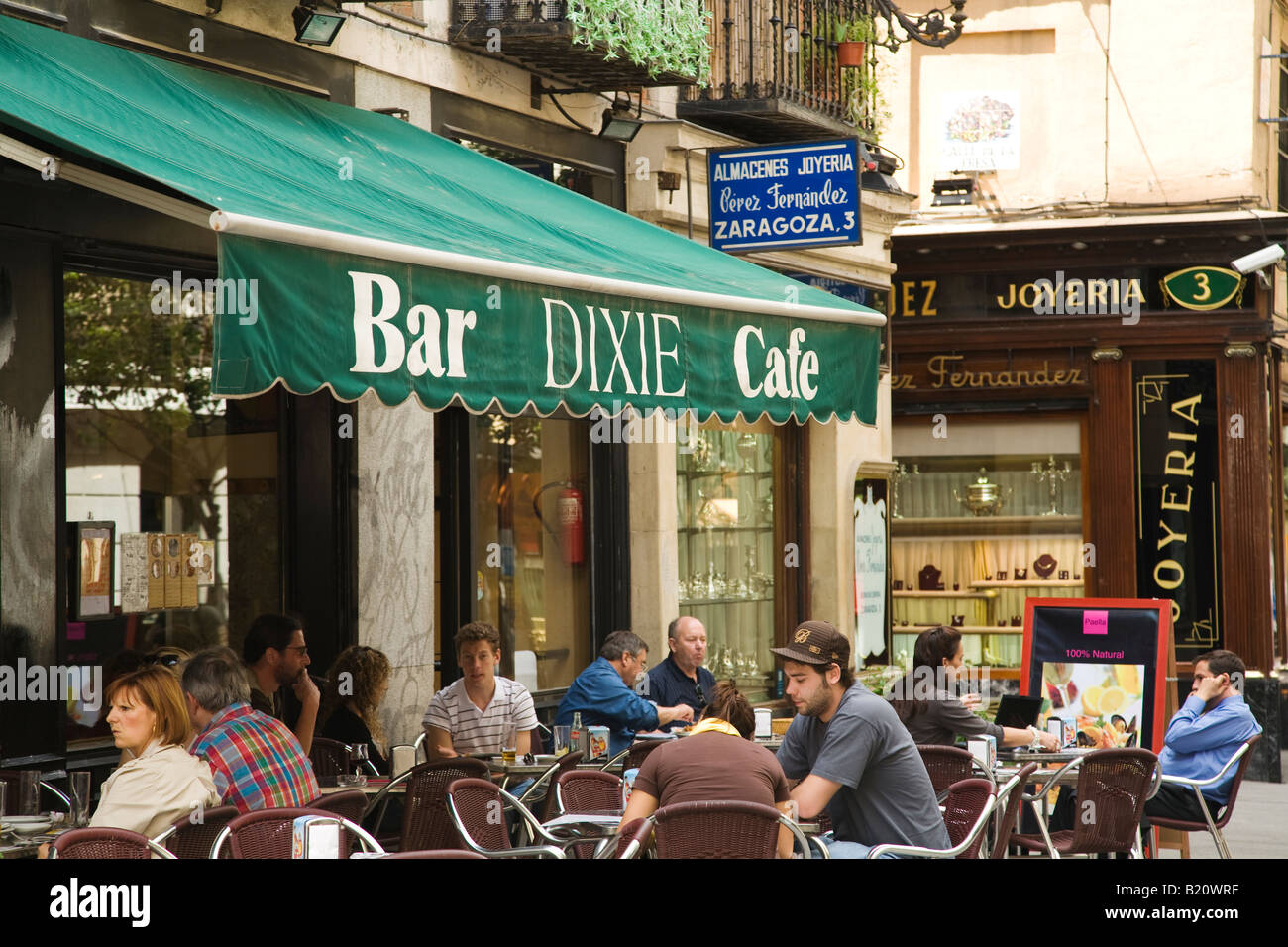 SPAIN Madrid People sitting at outdoor tables at Dixie Bar and Cafe green awning at restaurant English name in Spanish - Stock Image