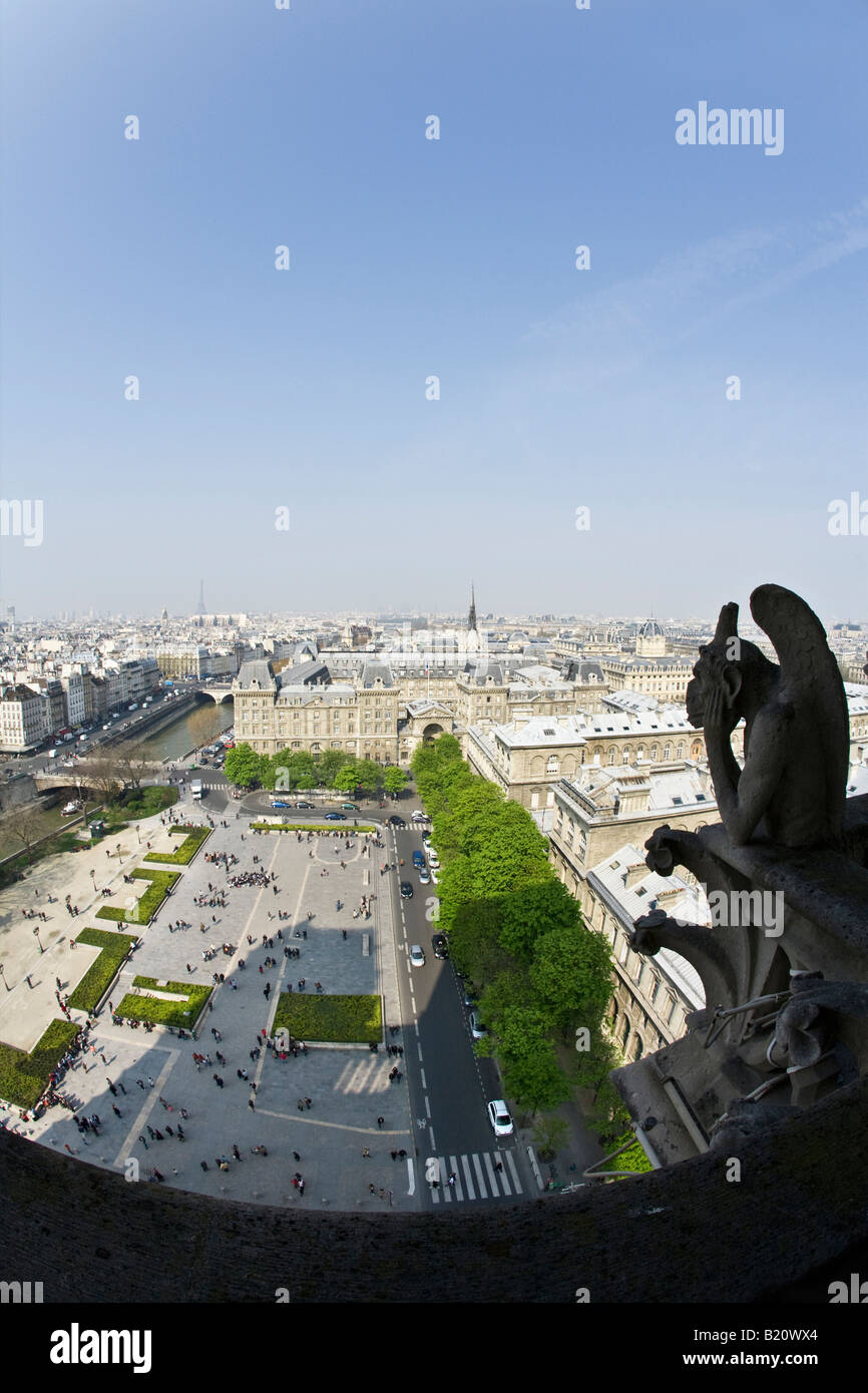 Notre Dame Cathedral gargoyles on exterior with scenic panoramic view over Paris in spring sunshine France Europe - Stock Image