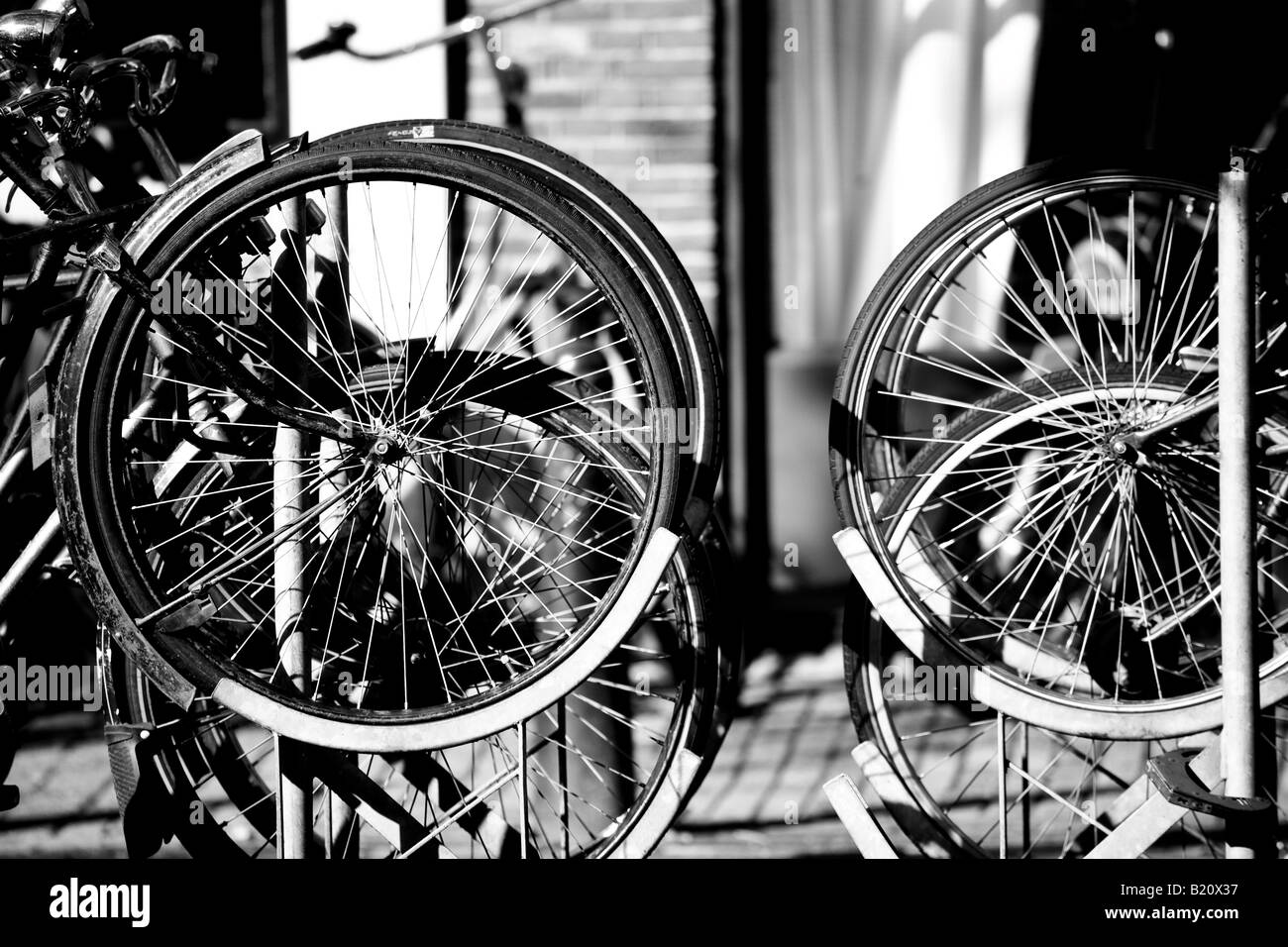 Bicyle Wheels in Bicyle Rack Parked next to a Canal in Amsterdam North Holland Netherlands - Stock Image