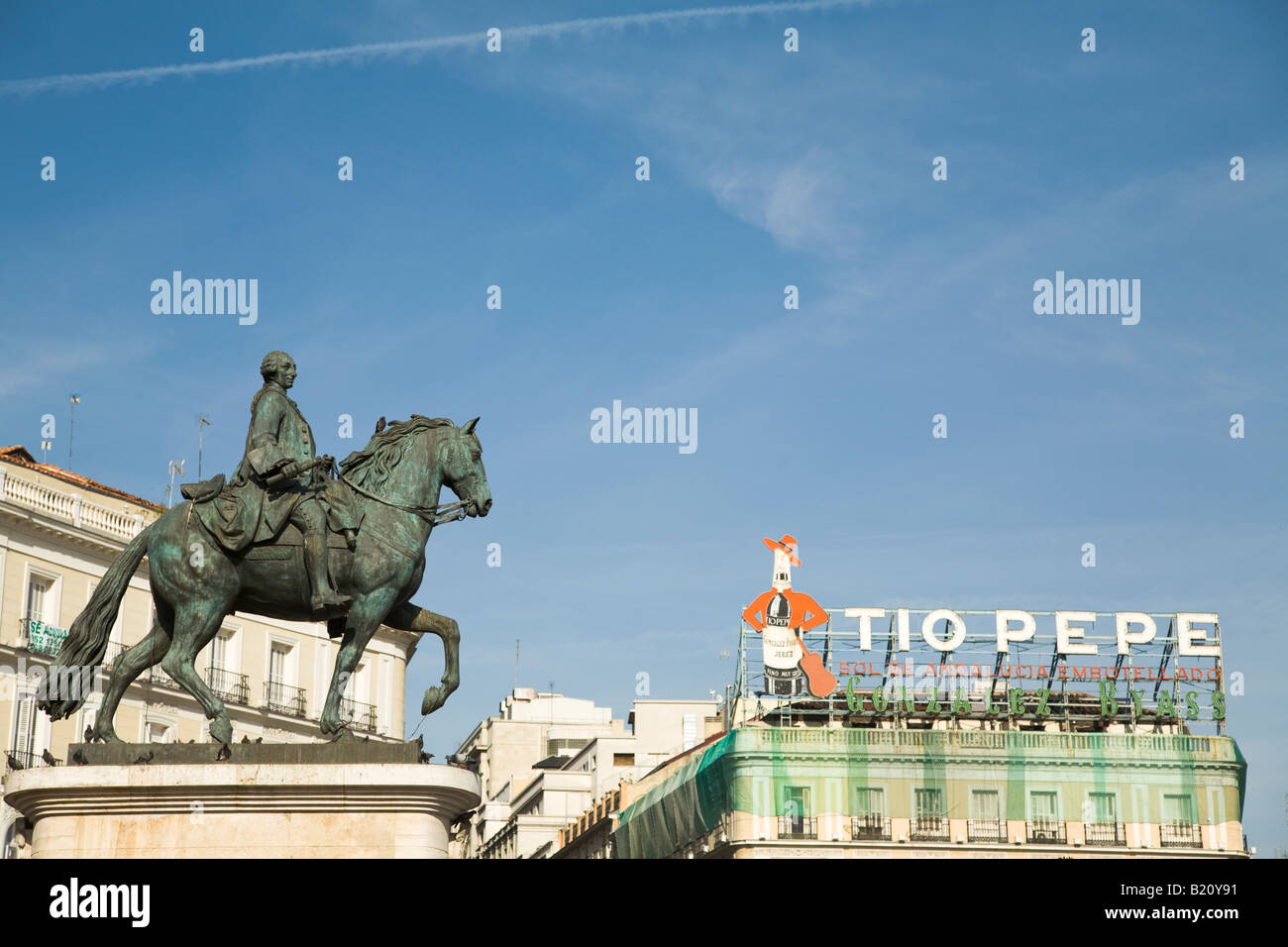 SPAIN Madrid Statue of Mounted King Charles III in Puerto del Sol plaza with Tio Pepe sign Stock Photo