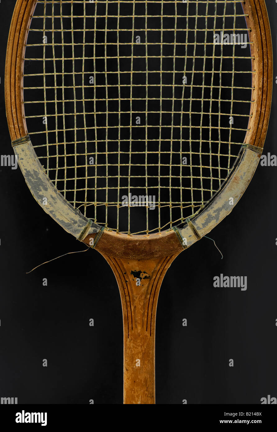 Vintage tennis racket shot against a black background - Stock Image