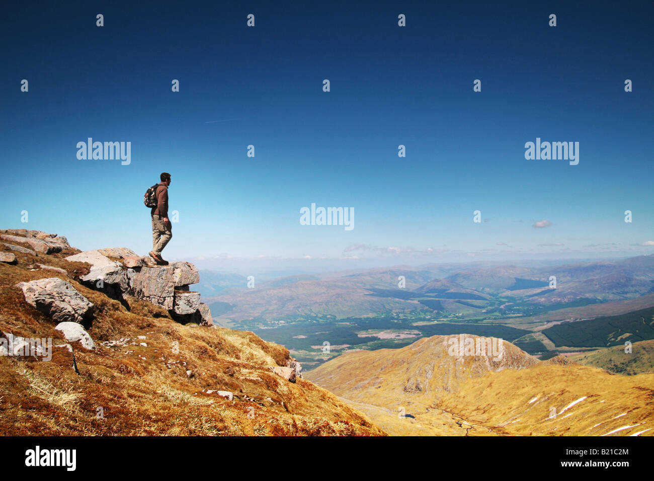 man stood at top of mountain looking at the view - Stock Image