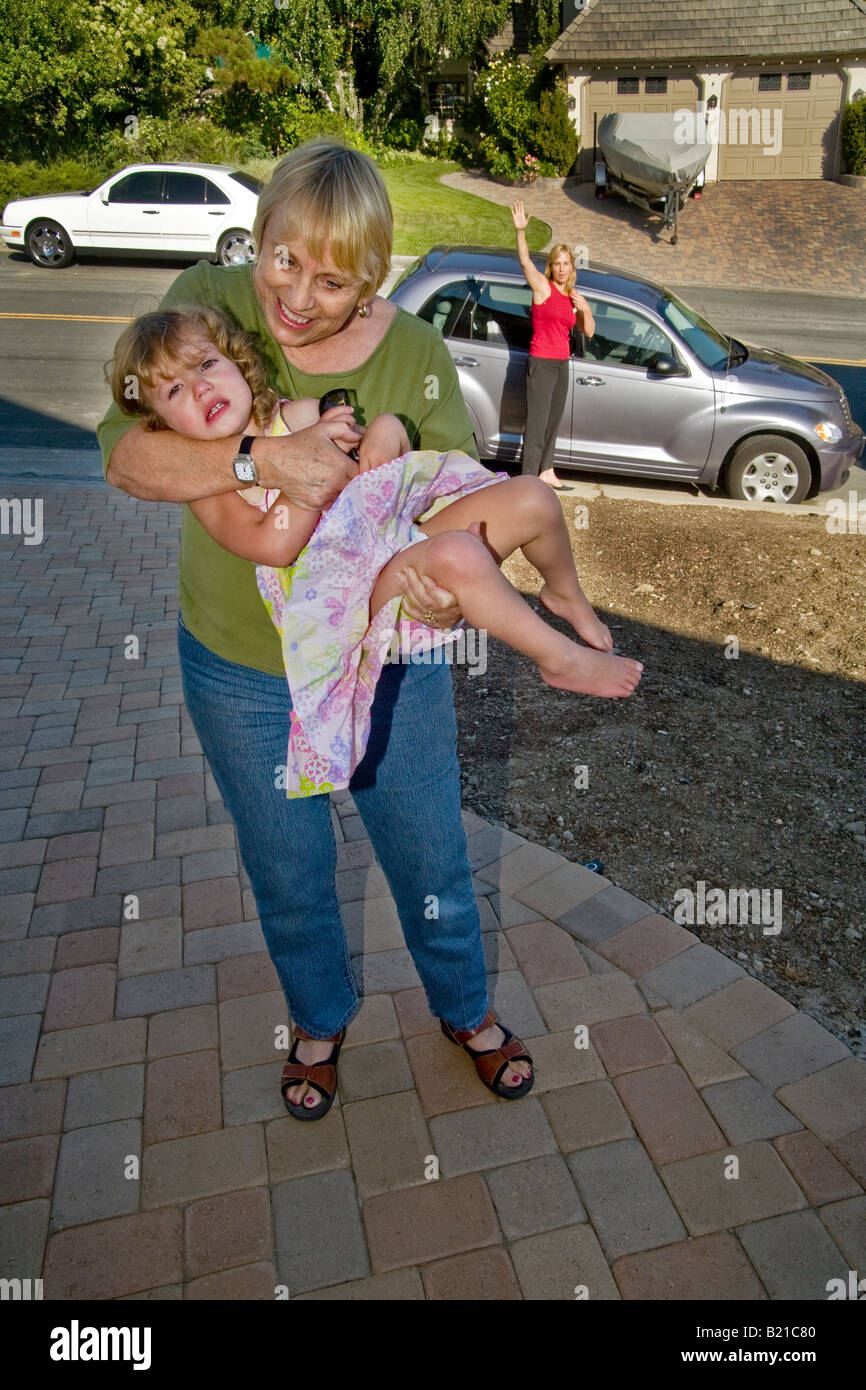 A two year old girl appears angry and confused as her mother background leaves her off for day care with grandmother - Stock Image