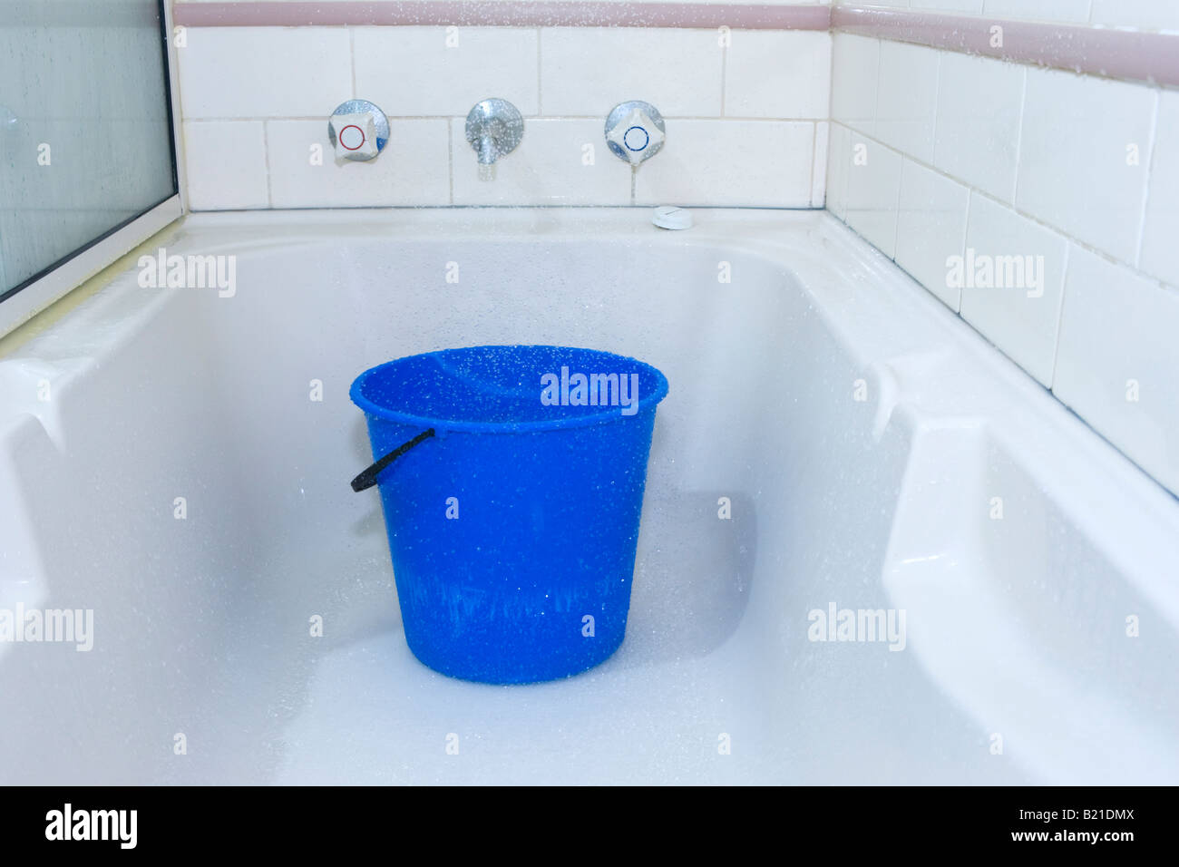A bucket placed in a bath under the shower to conserve water so it ...