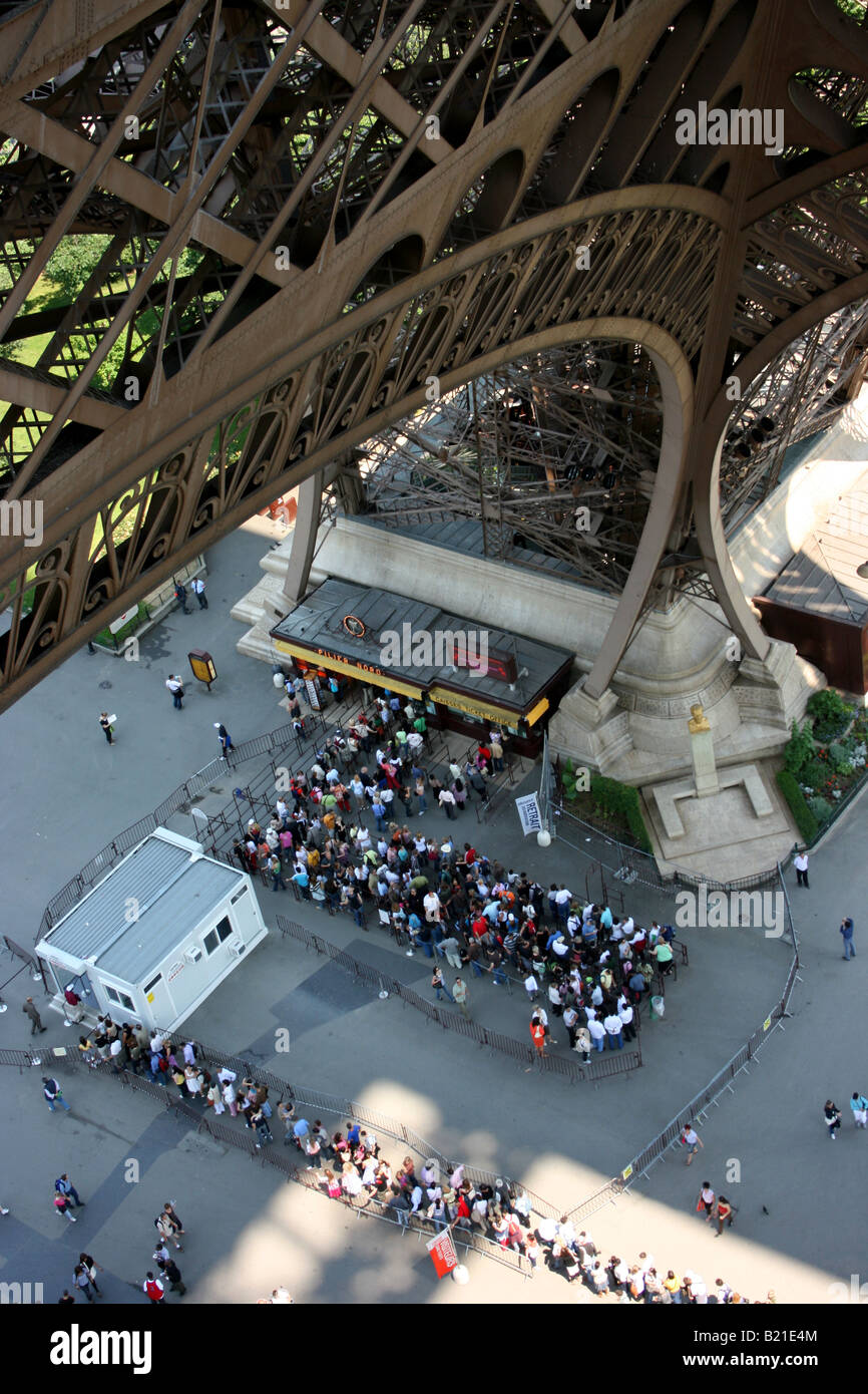 looking down from the first level of the Eiffel tower to the queues of tourists waiting to ascend at the base of - Stock Image