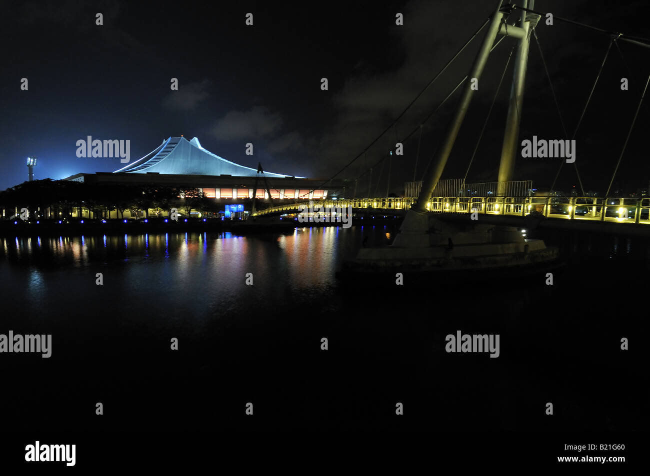 Singapore Indoor Stadium and bridge over Kallang river at night - Stock Image