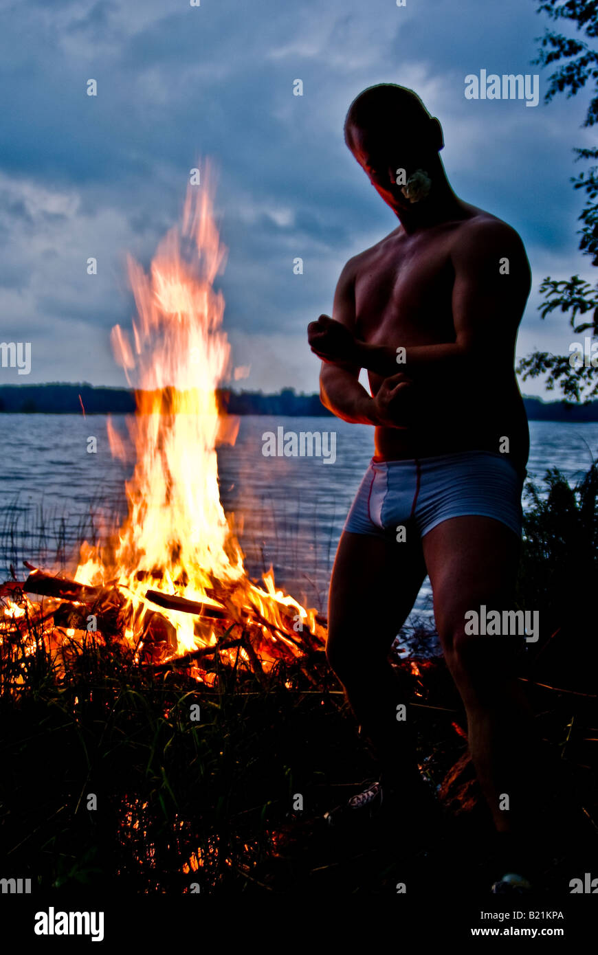 A crazy finn flexes his muscles next to a traditional finnish midsummer pyre - Stock Image