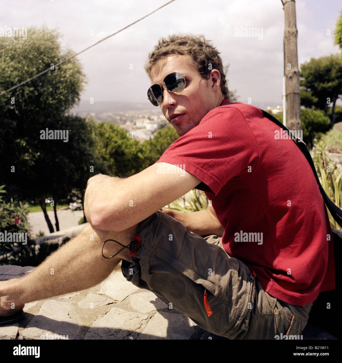 Gap year student in shorts and red tee shirt sitting on a wall looking towards the camera - Stock Image