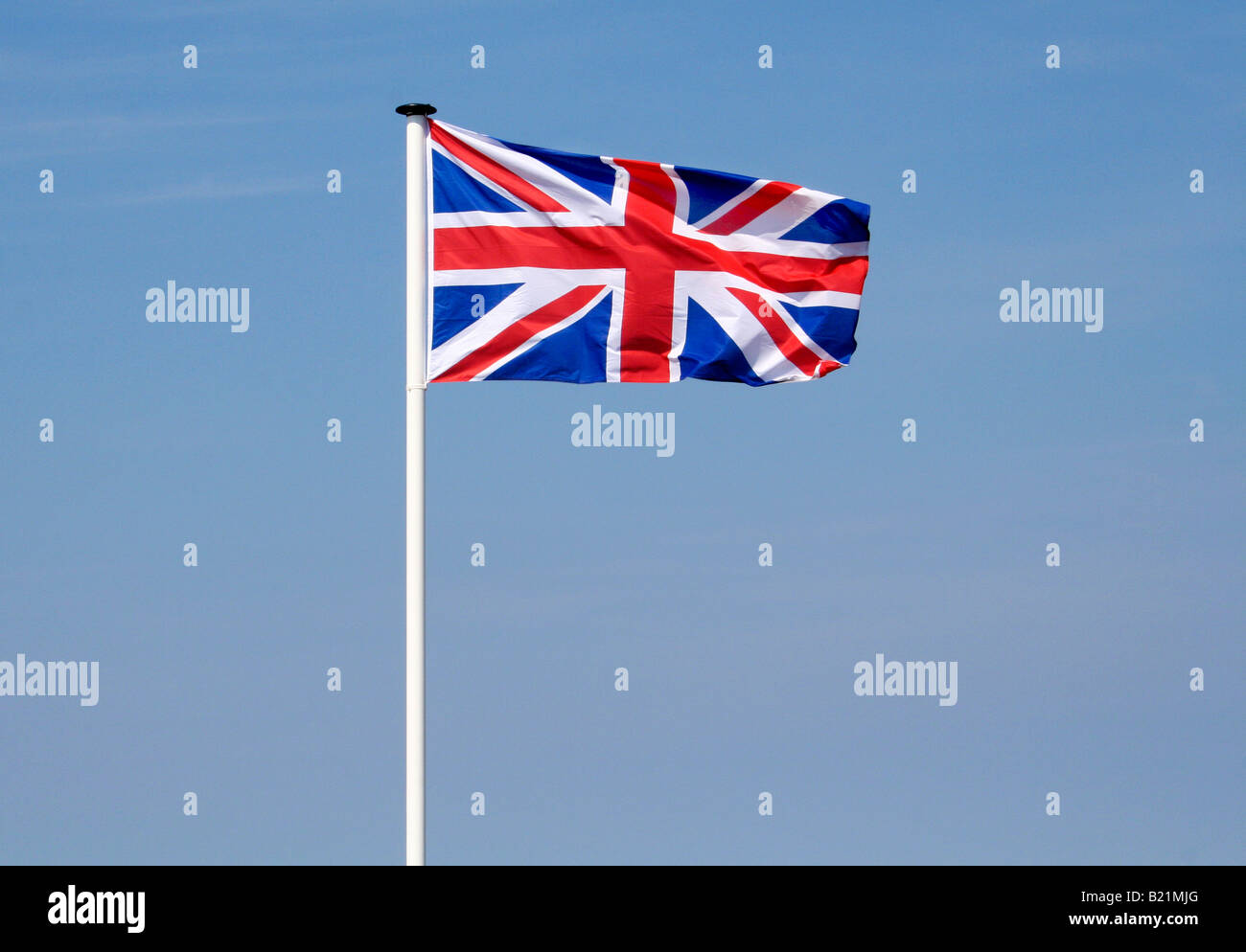 Union Jack flag on a white flagpole fluttering in the breeze. - Stock Image