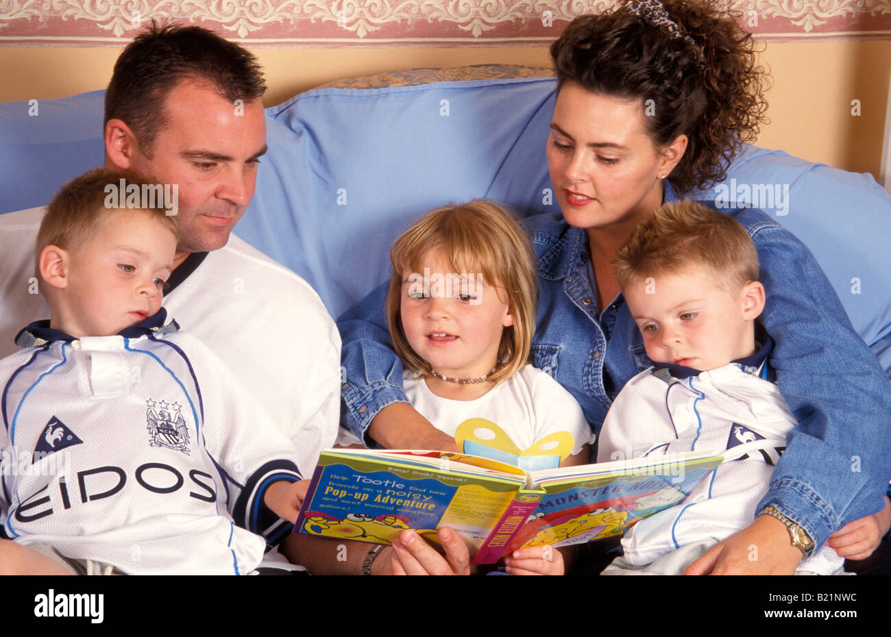 mother and father reading story to twin boys and daughter - Stock Image