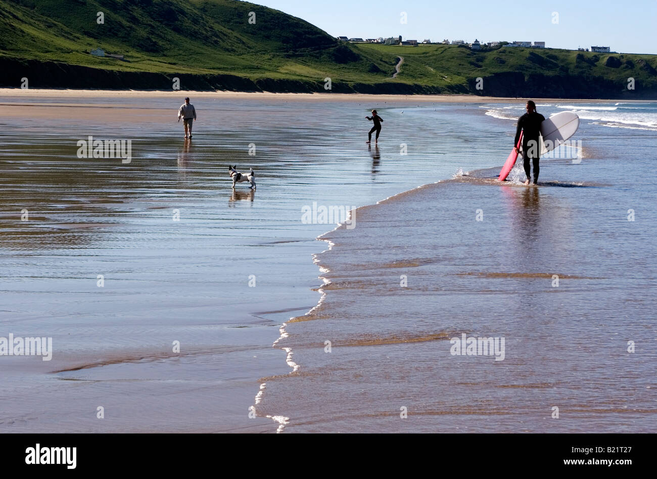 A surfer and his family & dog walk down the beach on the beautiful bay of Rhossili near Llangennith, Gower Peninsular, - Stock Image