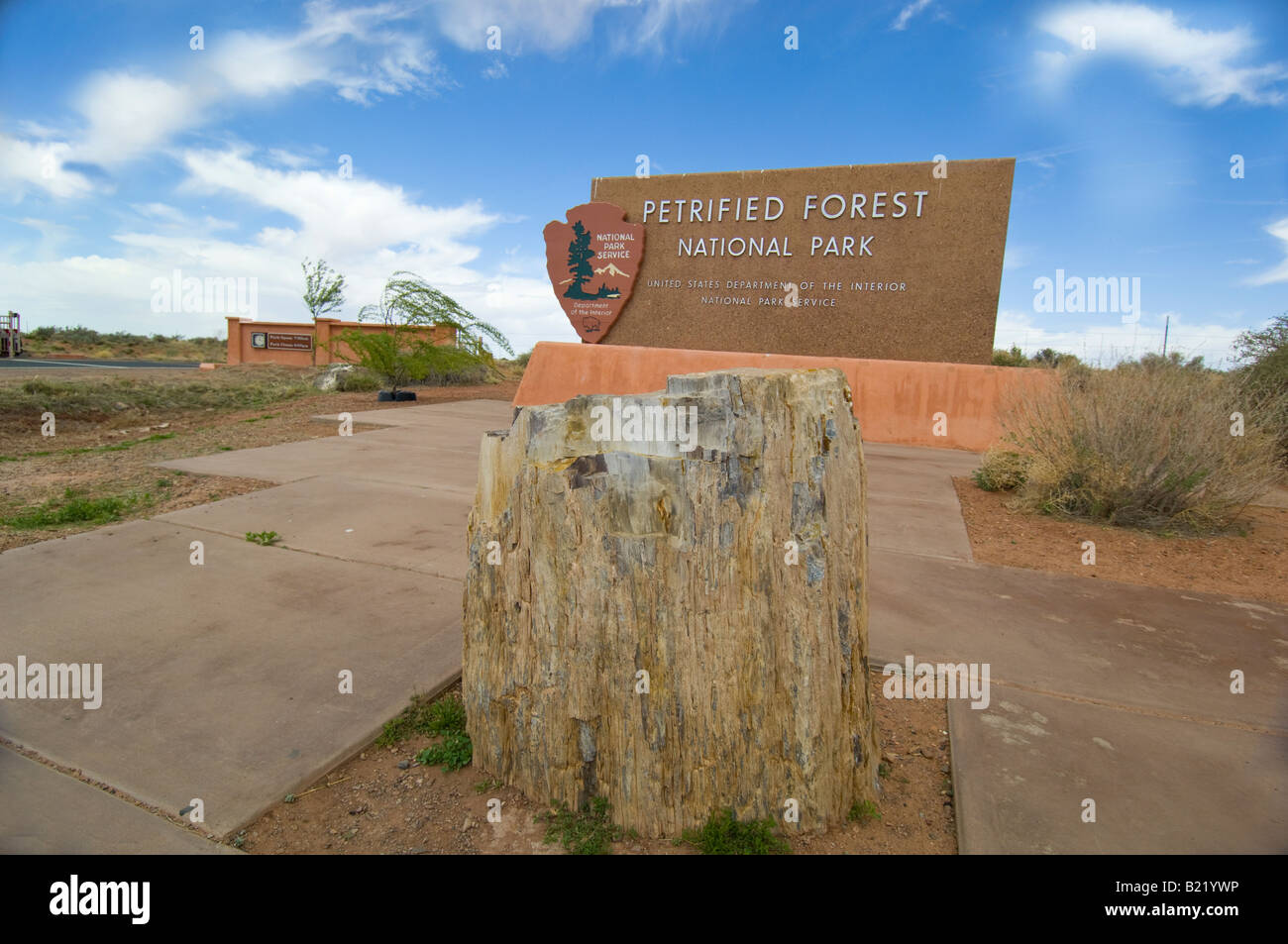 Petrified log in front of Petrified Forest National Park sign - Stock Image