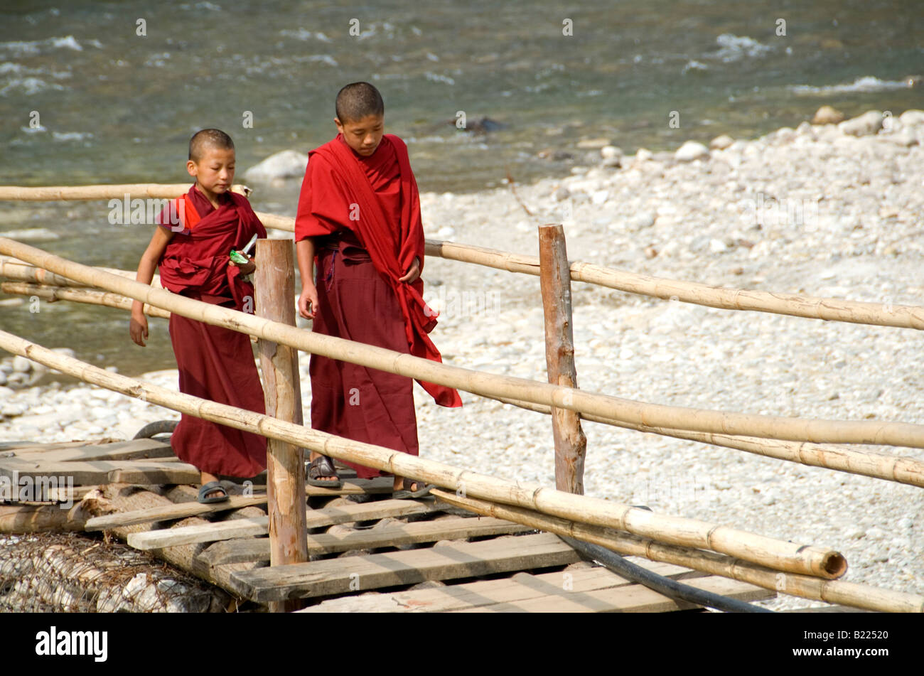 Two young monks walking to Punakha Dzong along temporary bamboo suspension bridge over Mo Chhu (Mother River) - Stock Image
