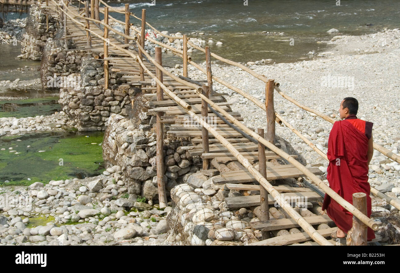 Monk walking to village from Punakha Dzong along temporary bamboo suspension bridge over Mo Chhu (Mother River), - Stock Image