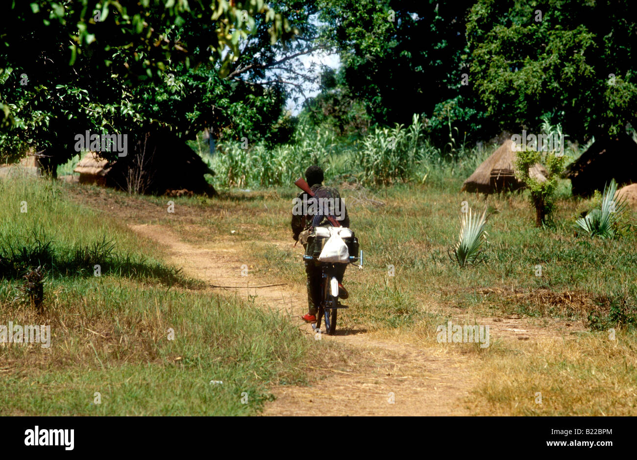Soldier in Southern Sudan, Africa cycles through a village with a gun on his back - Stock Image