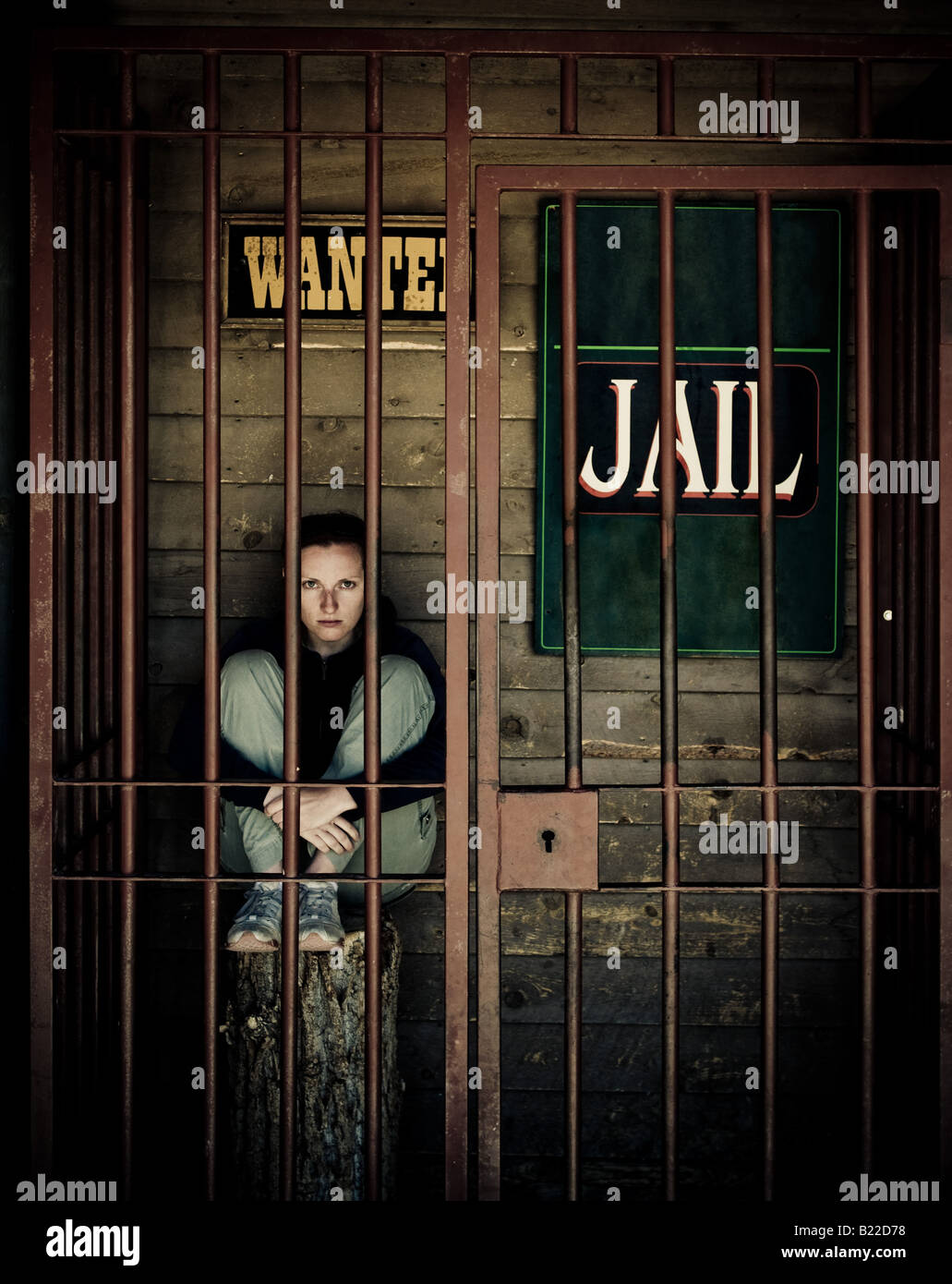behind the bars young woman sitting in jail - Stock Image