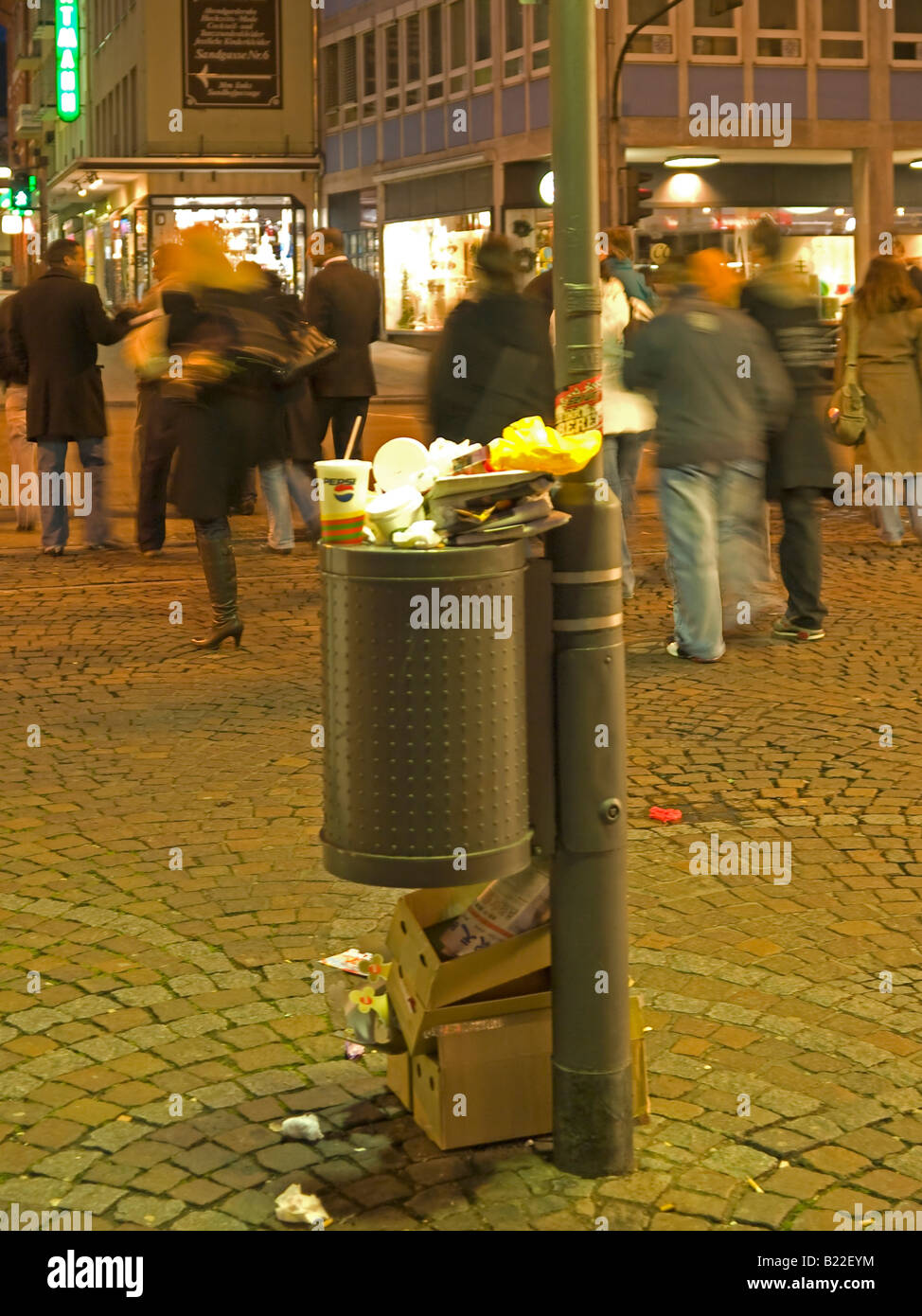 trash rubbish garbage and a full waste bin garbage can in pedestrian area in the night in the city Frankfurt am - Stock Image