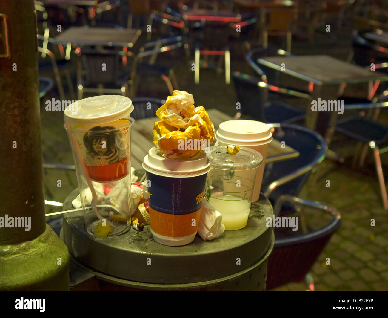 full rubbish bin at a outdoor restaurant on the street at night in Frankfurt am Main Hesse Germany - Stock Image