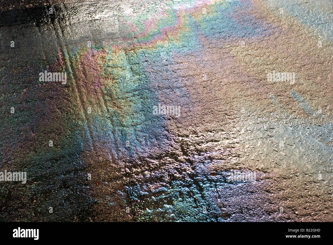 oilslick on wet tarmac with refracted light colours - Stock Image