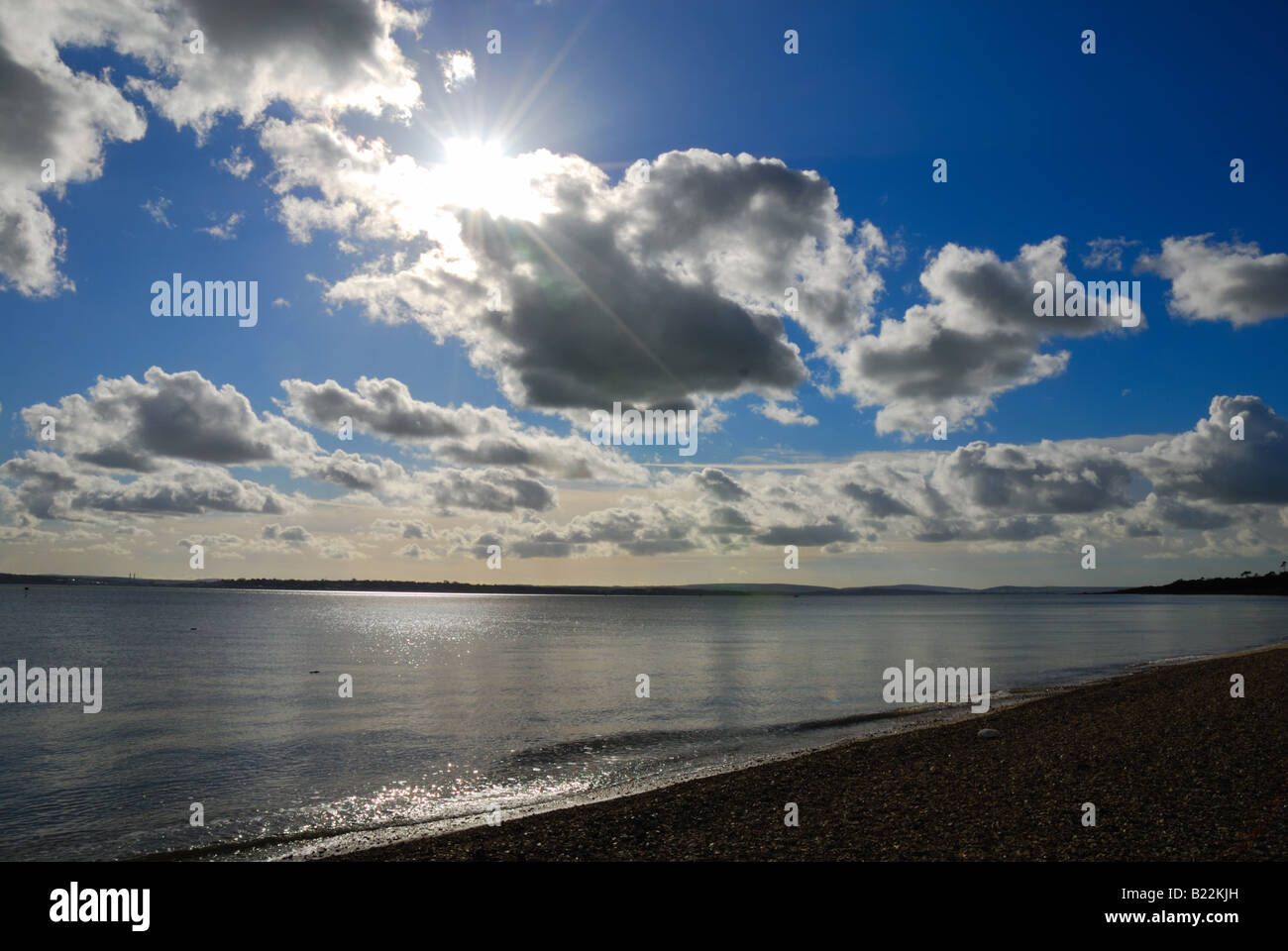 Sun through clouds with beach and sea in foreground at Calshot Hampshire England UK - Stock Image
