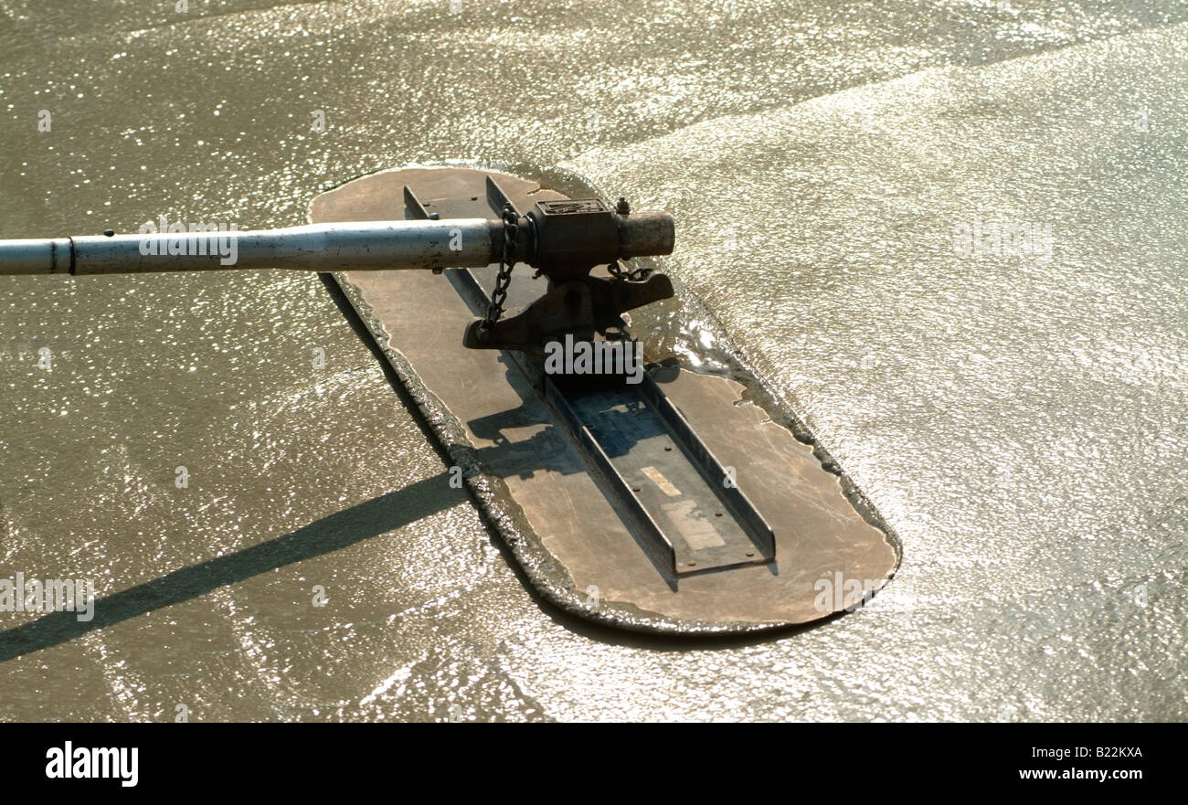 Workman Bullfloating wet concrete during construction of a driveway in front of a private home in San Jose, California. - Stock Image