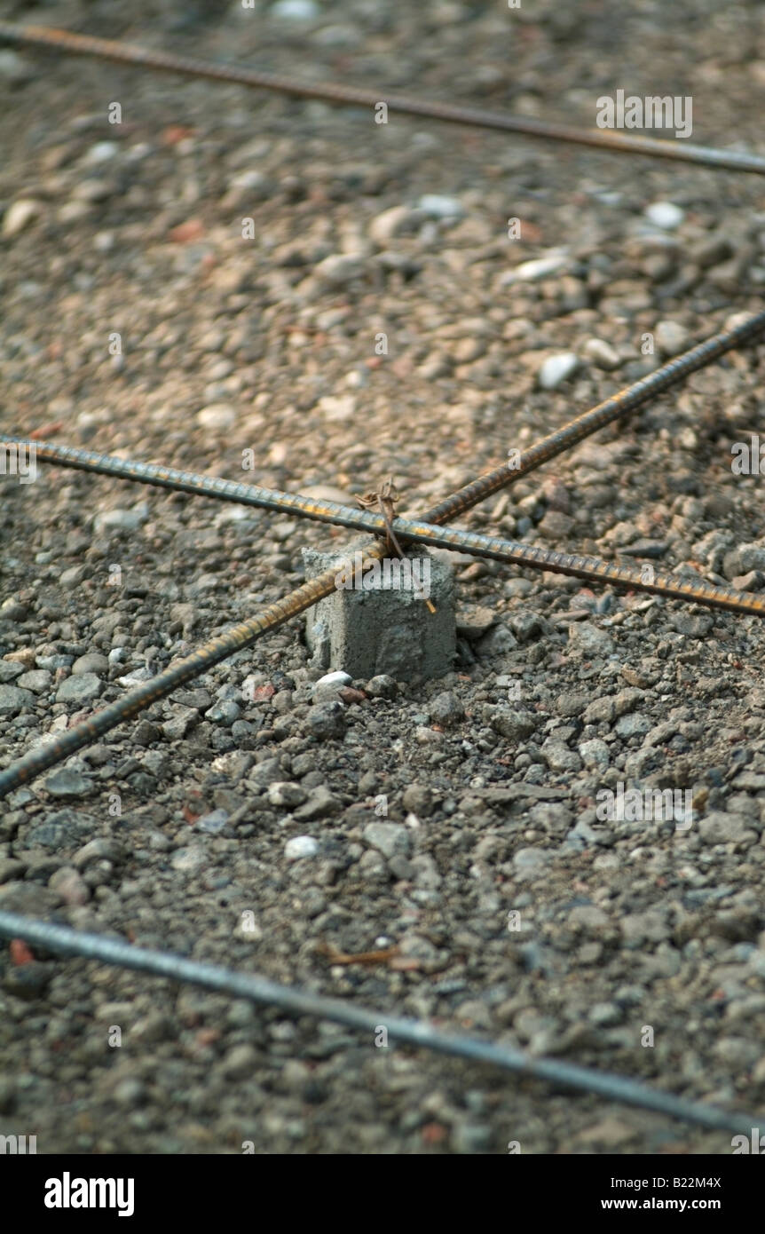 Steel Rebar rods supported by a small concrete box before concrete slabs are pored making the driveway of a private - Stock Image