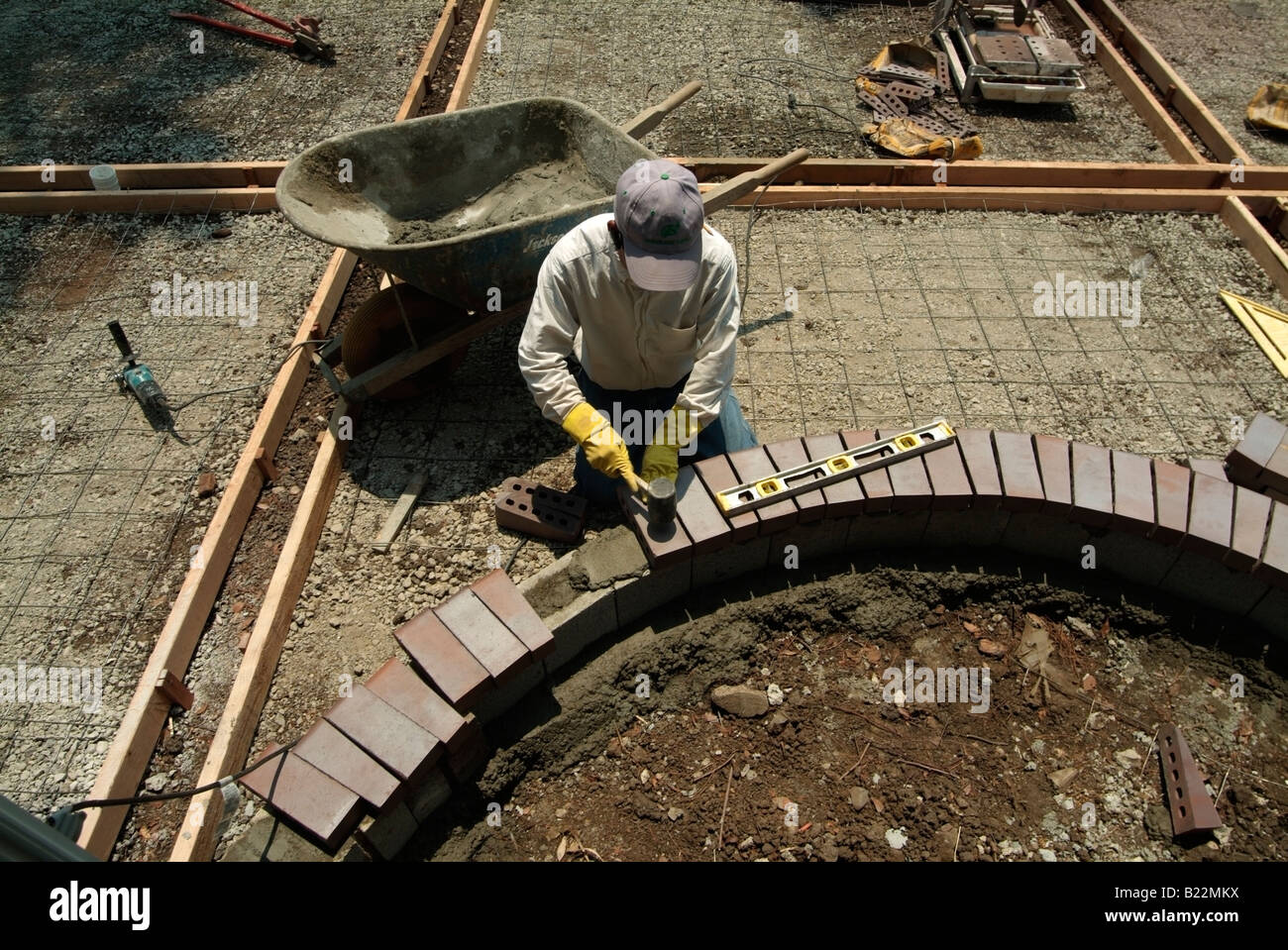 Workman leveling bricks to make a step to a backyard patio in Silicon Valley, California. - Stock Image