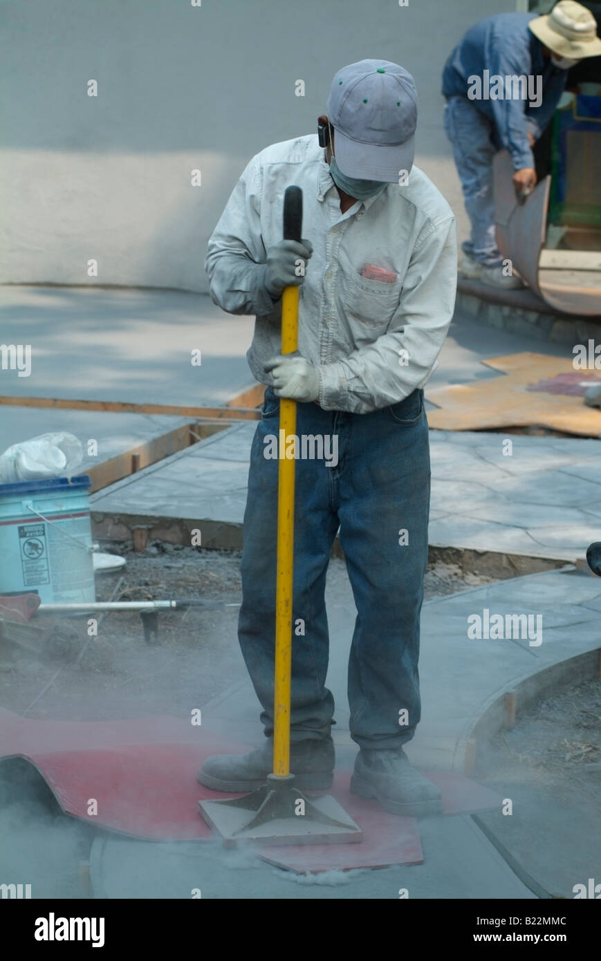 Workman stamping a texture into fresh concrete during construction of a patio in the backyard of a private home Stock Photo