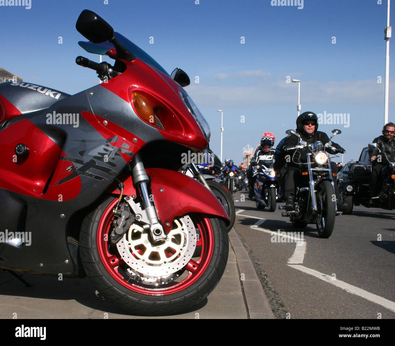 Chopper riders cruise past a Suzuki Hayabusa GSX1300R hyper sport motorcycle Hastings May Day bike festival Sussex, Stock Photo