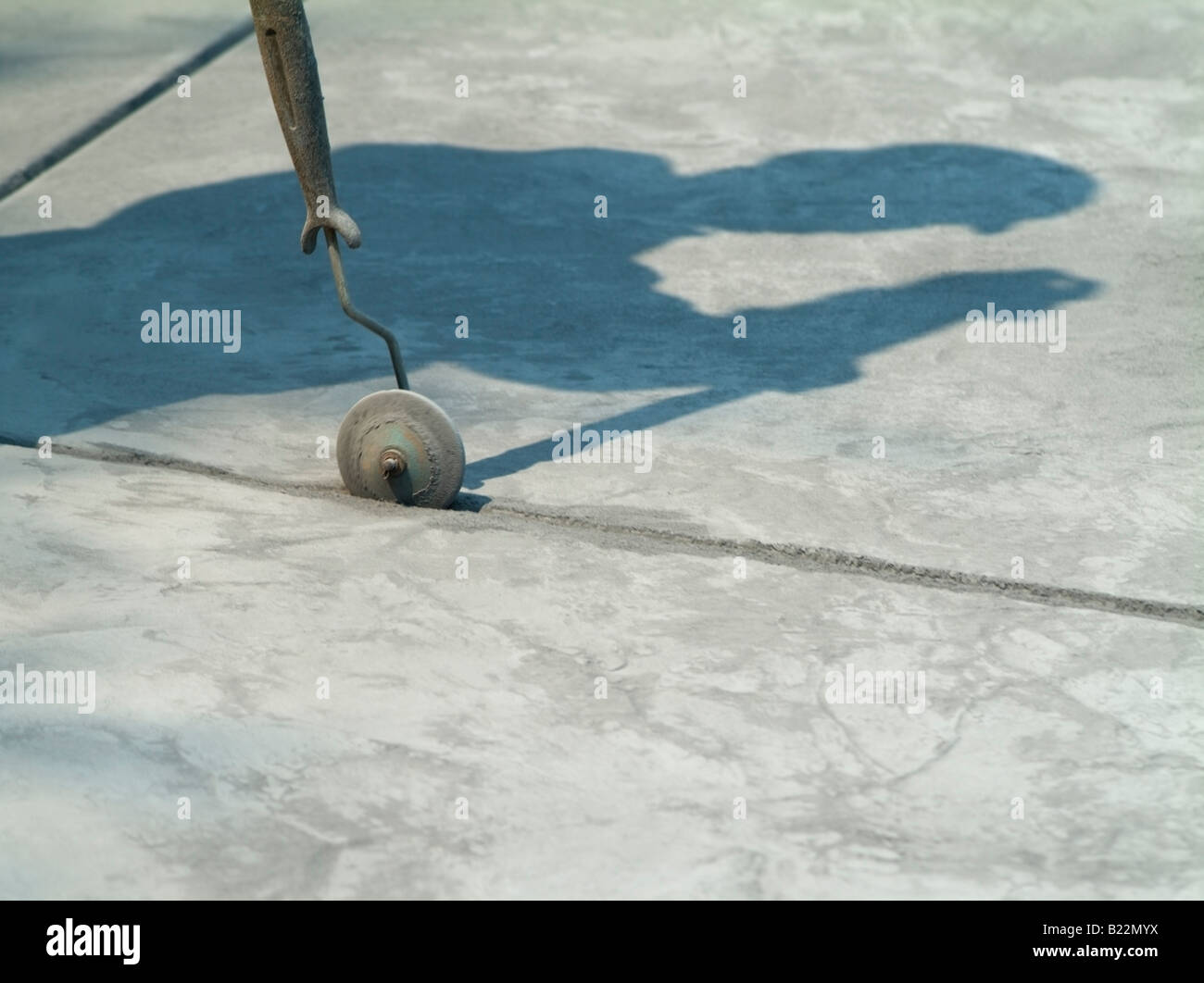The shadow of a Workman using a trowel to finish a line in wet concrete in the driveway of a private home in San Stock Photo