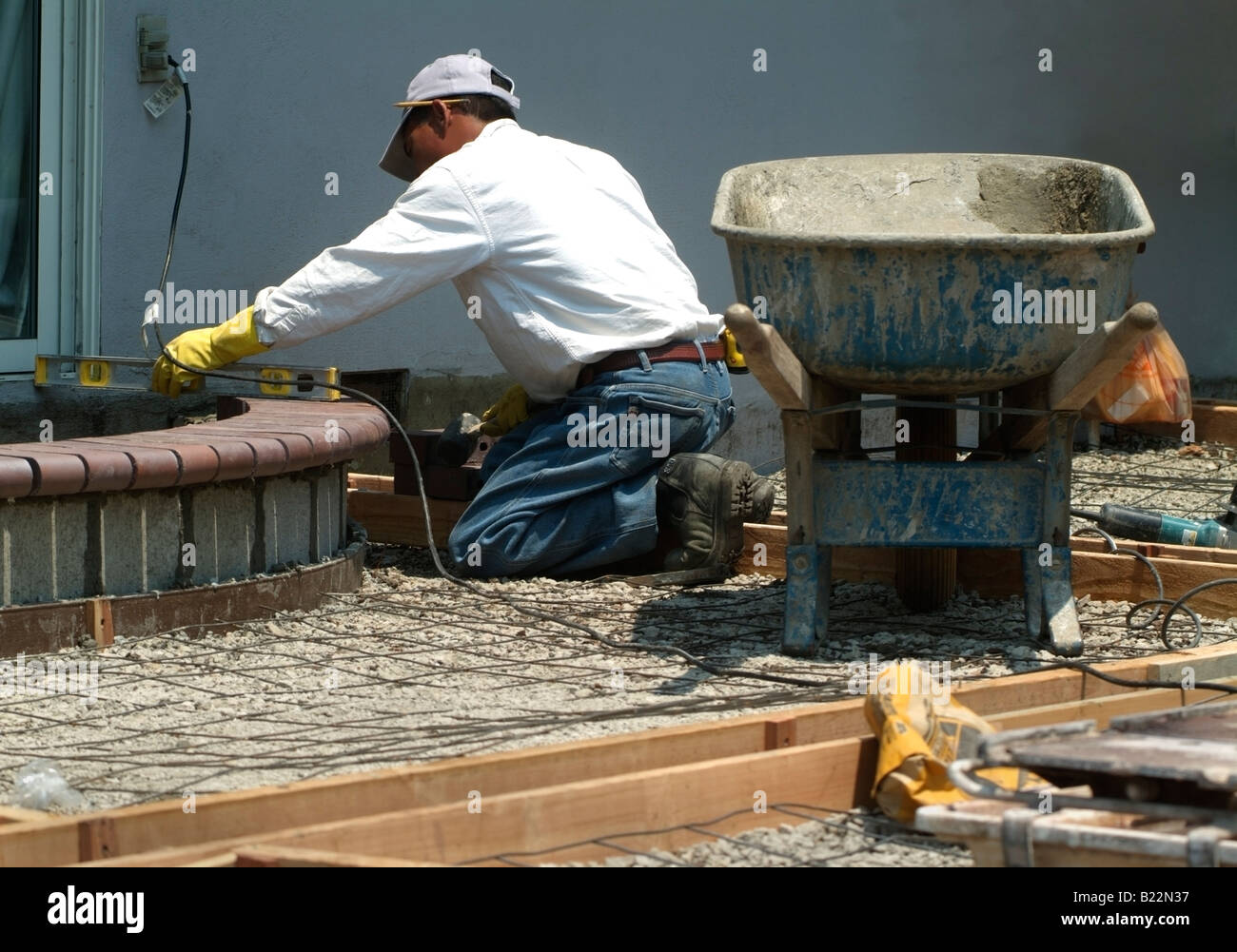 Workman leveling bricks to make a step to a backyard patio in Silicon Valley, California. Stock Photo