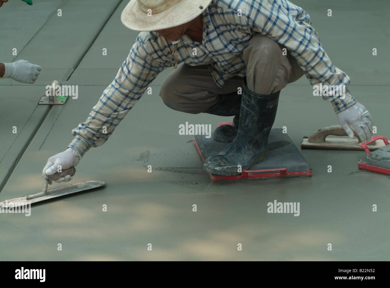 Workman leveling wet concrete with a Darby while another workman uses an edging tool to groove freshly poured concrete - Stock Image