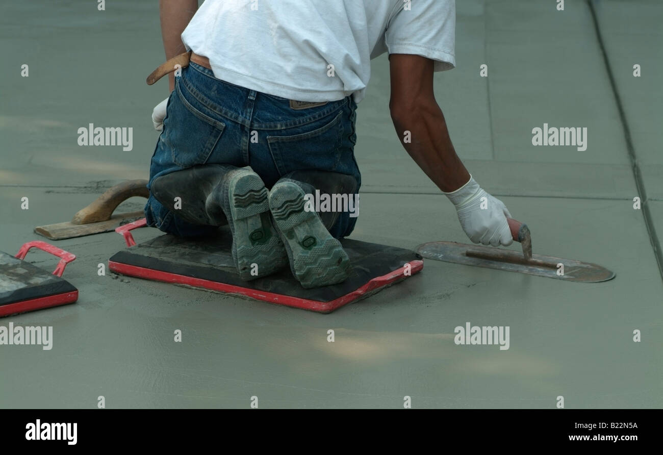 Workman leveling wet concrete with a Darby during construction of a driveway in front of a private home in California. Stock Photo