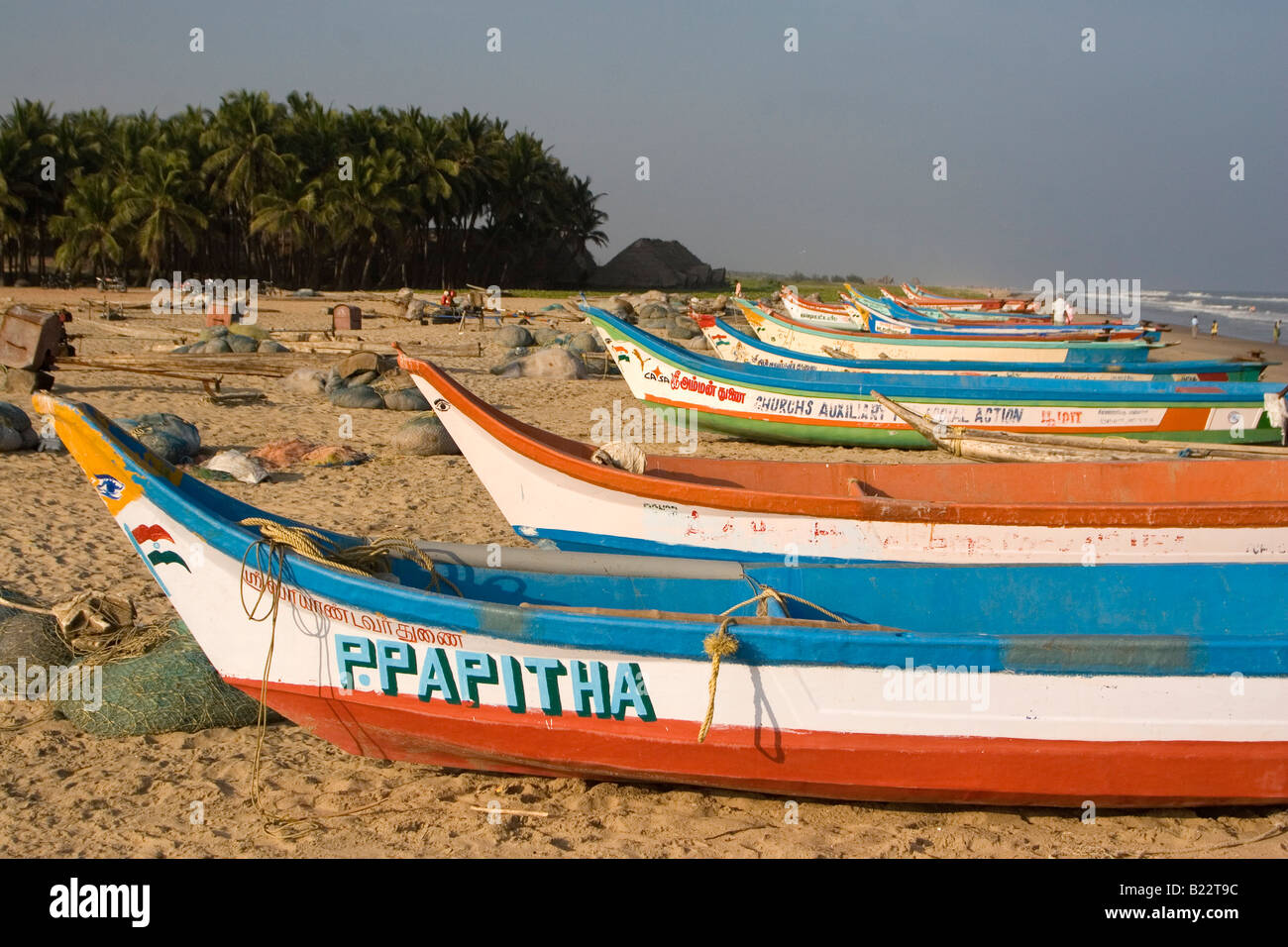 Fishing boats on the beach in Puducherry (the new name for Pondicherry) in South India. The boats are red, white - Stock Image
