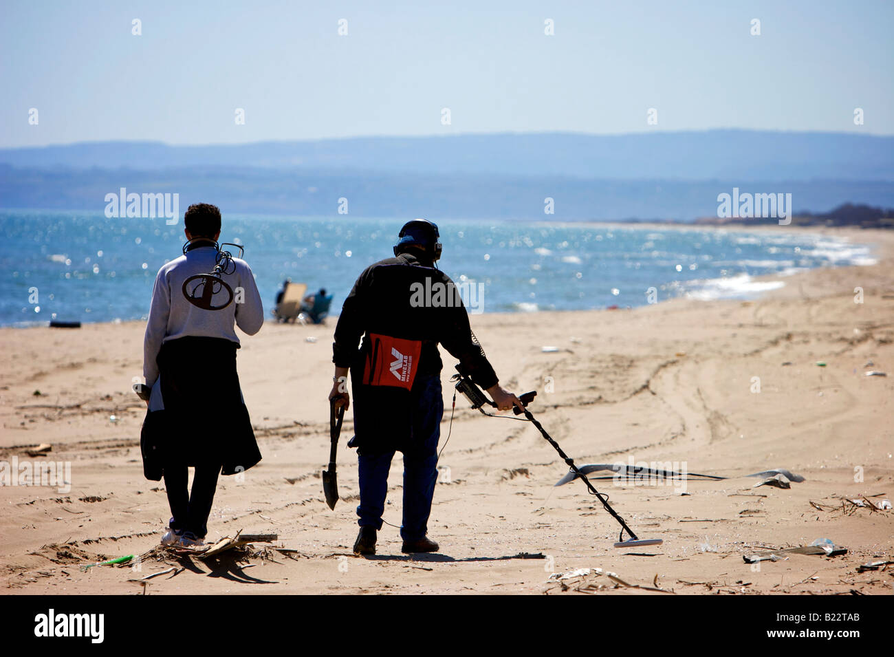 Men with metal detector search for hidden valuables on the beach at Catania, Sicily, Italy - Stock Image
